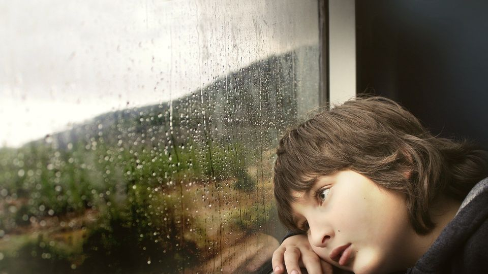 Child looking sad staring out of a window.